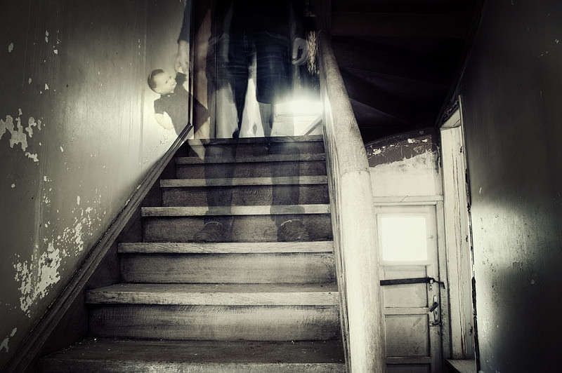 Ghost walking down stairs with doll - haunted house signs
